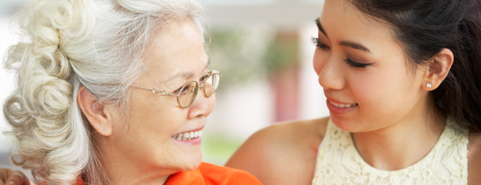young woman and senior woman smiling each other